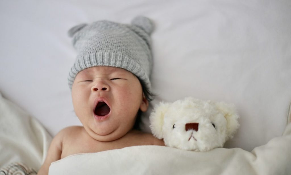 photo of a baby yawning with a teddy bear beside them and a cute grey panda hat on