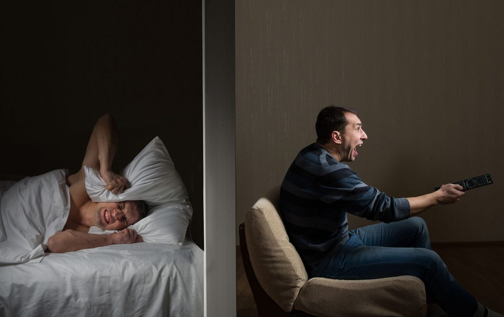 photo of two men split screen view with one screaming with pillow over head, other screaming holding TV remote
