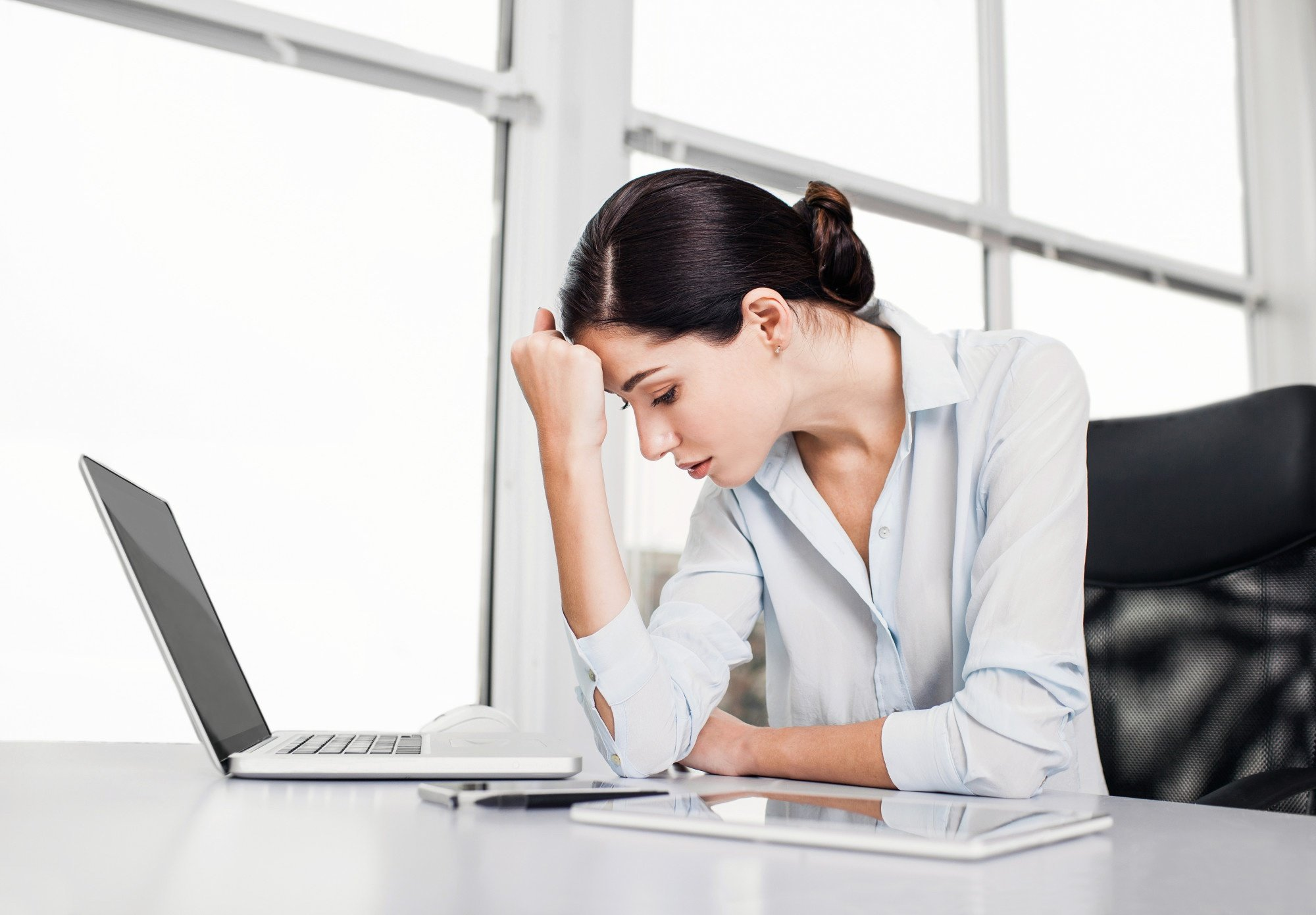 woman with hand on head sitting at desk with laptop looking upset