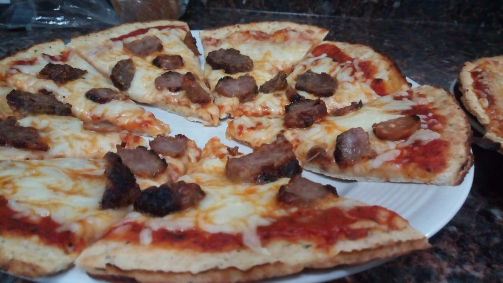 photo of family meal planning homemade pizza for pizza friday night. a sausage pizza.