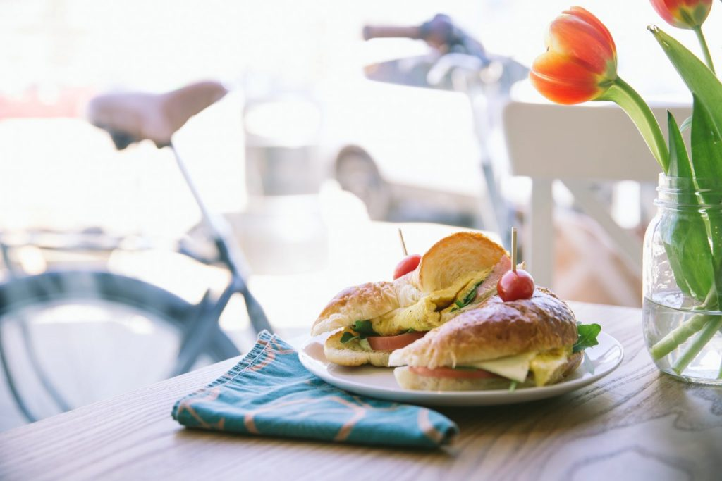 photo of a table with breakfast sandwich on it and tulips off to the right.