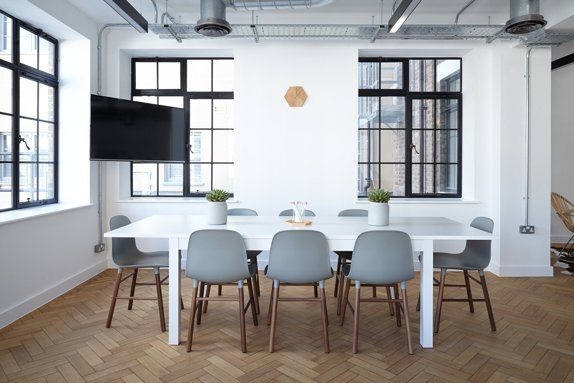 image of offiice with table and chairs. Two windows and a big screen tv to the right of the table