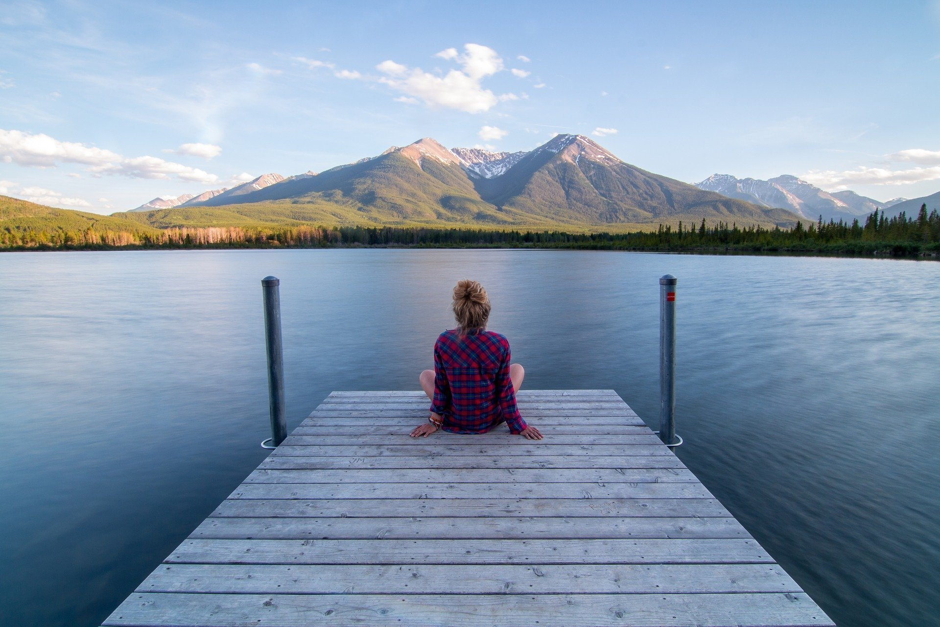 photo of a girl with hair in a bun sitting at the end of a dock watching the water with a moutain view letting things go