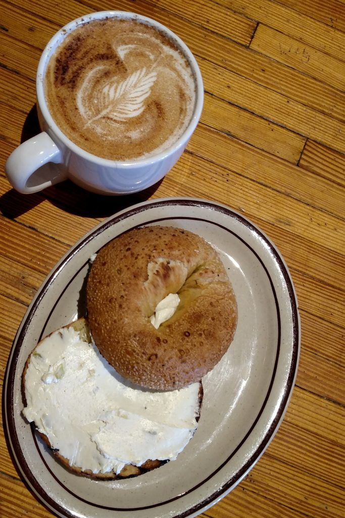 photo of a bagel with cream cheese and a cup of coffee on a brown wood table