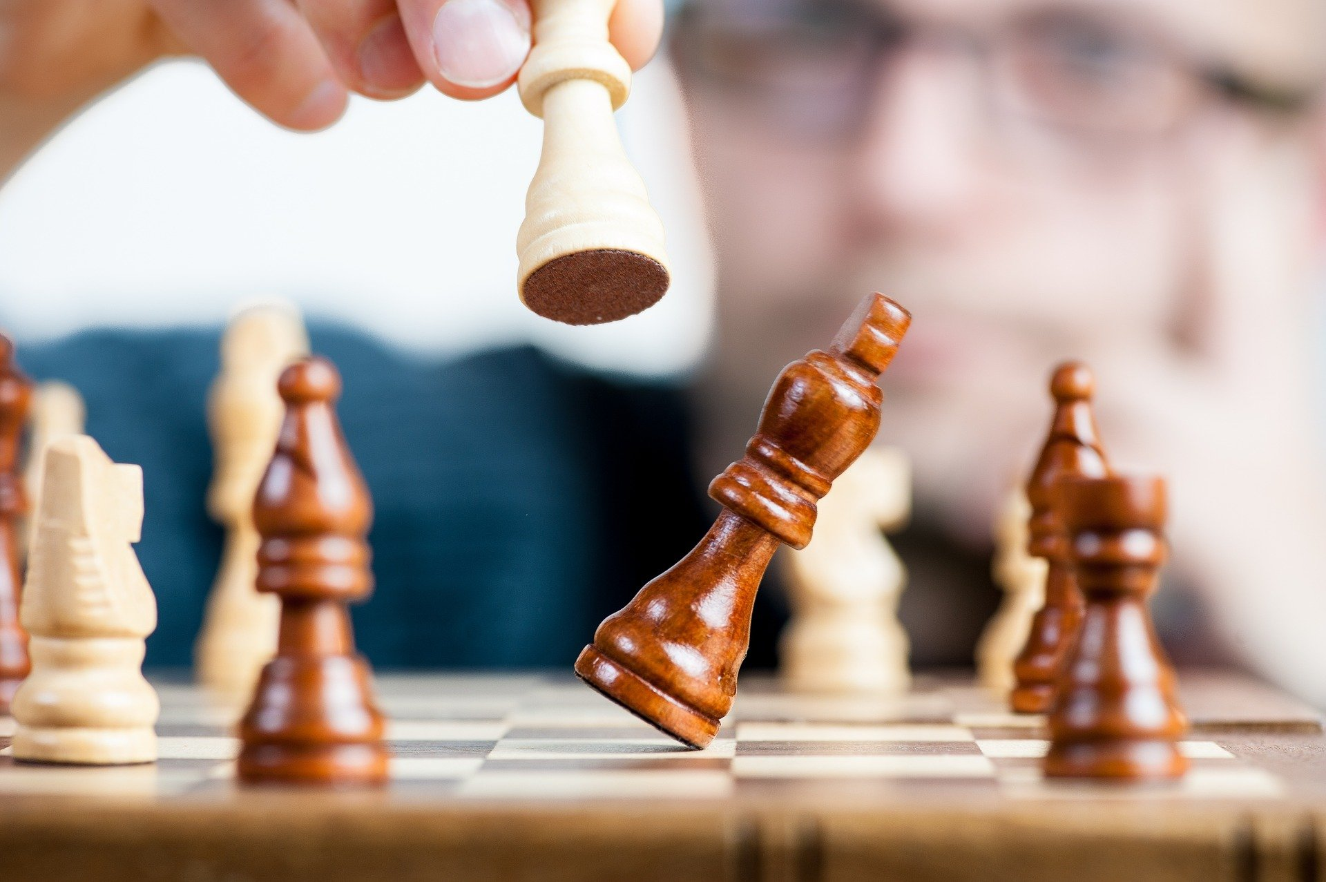image of a person putting over the king on a brown and white chess board