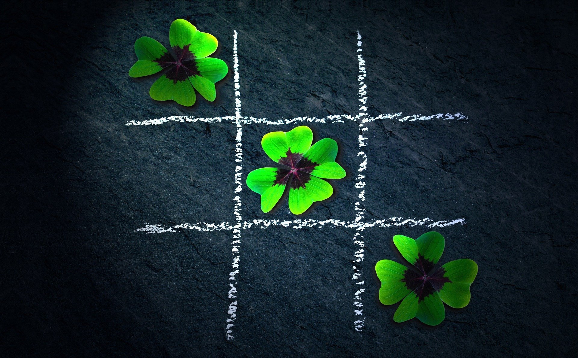 phoot of a black background with tic tac toe in white and three green flowers in a row